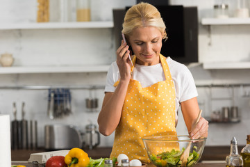 smiling mature woman in apron talking by smartphone while cooking vegetable salad
