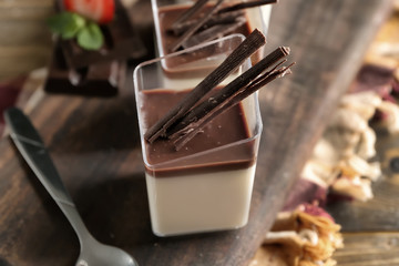 Glasses with tasty chocolate panna cotta on wooden board, closeup