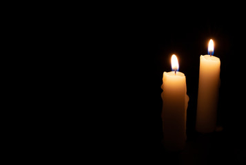 Two candles on black background. Lighting candles in darkness. Yellow wax candle with warm flame. In memoriam banner