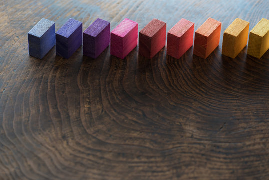 Colored wooden blocks diagonally aligned on a old vintage wooden table. For something with concept of variations or diversity. Plenty of copy space for cover or header image usage.