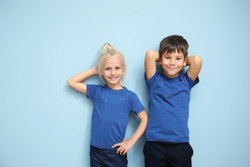 Boy and girl in t-shirts on color background
