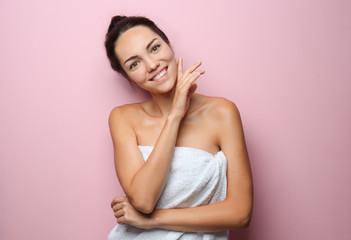 Beautiful young woman wrapped in towel on color background