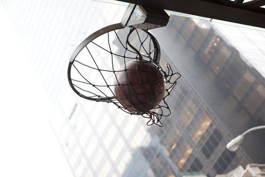canasta de baloncesto en mitad de una calle de manhattan con  edificios de fondo