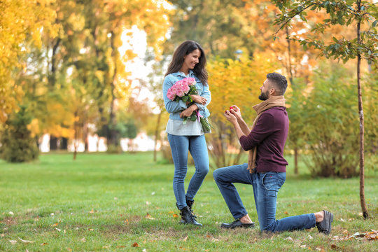 Young man proposing to his beloved in autumn park