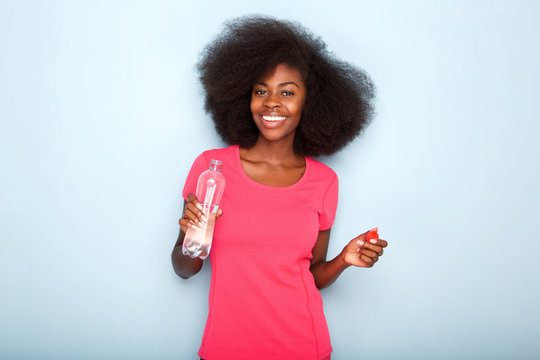 Close up happy young black woman holding bottle of water