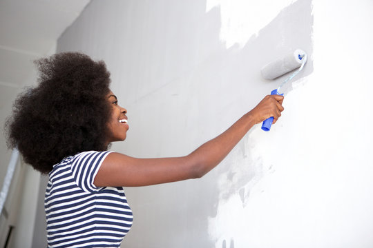 young black woman painting wall at home