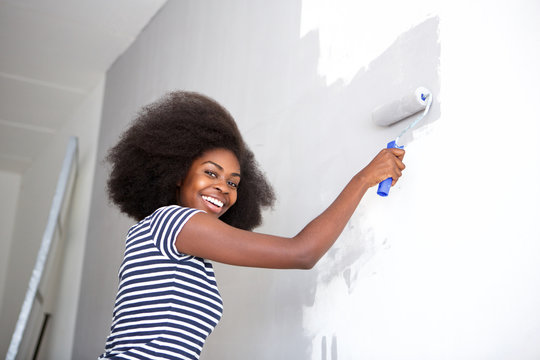 young african american woman painting wall at home