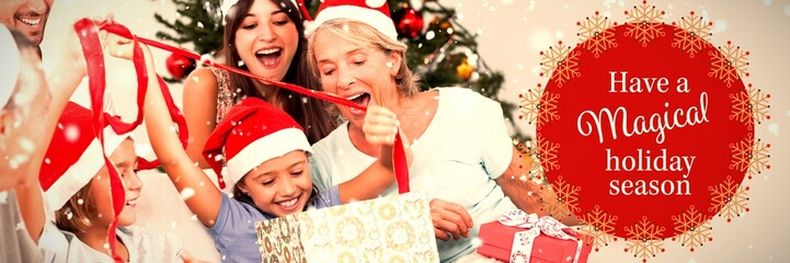 Composite image of happy family at christmas opening gifts