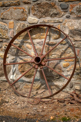 Rusty cart wheel resting against a stone wall no. 2