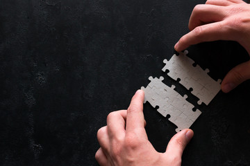 businessman connects two pieces of puzzle business concept on black background with place for text