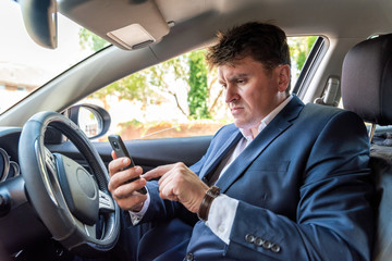 Businessman texting on smartphone inside car on bright day