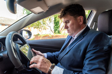 Businessman working on tablet inside car on bright day