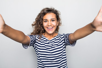 Portrait of a smiling young mixed race mulatto woman taking selfie with mobile phone over gray background