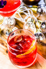 A red coloured cocktail with ice cubes and a twist of lemon