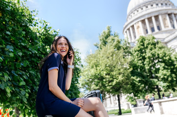 UK, London, laughing young woman talking on the phone near St. Paul's Cathedral