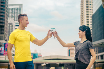 Sport woman and man two hands horizontal holding water bottles and clinking on building background.