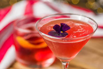 A red colored cocktail with a purple flower, with other cocktails in the background
