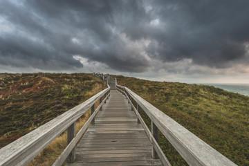 Germany, Schleswig-Holstein, Sylt, Wenningstedt, boardwalk to the beach under rain clouds