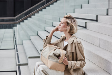 Fashionable blond businesswoman wearing beige trenchcoat sitting on stairs with travelling bag