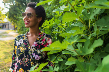 Smiling young woman wearing sunglasses and colourful blouse in a park