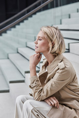 Young blond businesswoman wearing beige trenchcoat sitting on stairs