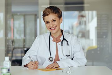 Portrait of a confident female doctor, filling in immunization card