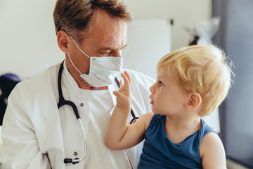 Toddler sitting on lap of pediatrician wearing protective mask