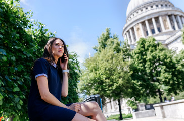UK, London, young woman talking on the phone near St. Paul's Cathedral