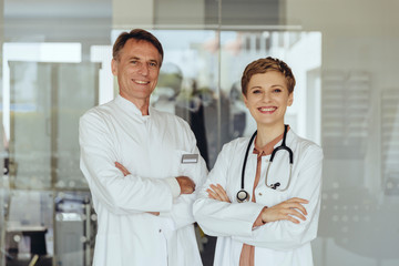 Two confident doctors standing in practice, with arms crossed