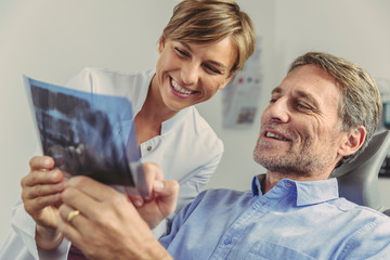 Dentist explaining x-ray image to smiling patient