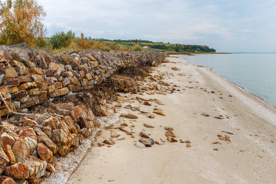 Coastal constructions with boulders in the metal net preventing the shore erosion. Taganrog bay, Azov sea, Russia