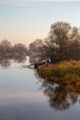 Fototapeta jesienny brzeg rzeki o wschodzie słońca z mgłą obraz