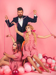 holidays and dolls. dominance and dependence. Crazy girls and man on pink. Halloween. vintage fashion women puppet and man. Creative idea. Love triangle. retro girls and master in party balloons