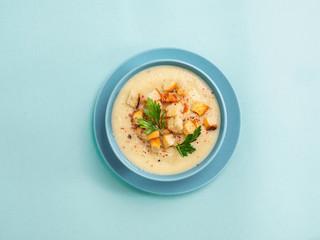 cauliflower soup puree on blue, top view