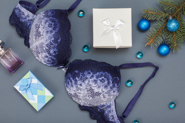 Blue lace bra and panties with gift boxes on gray background. Women underwear.