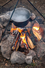 Cooking on a fire. Fish soup on a fire. Food in a cauldron on a fire. Food outdoors. Cooking outdoors. Cooking in nature on the cauldron.