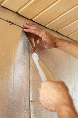 Male hands using aluminum tape to glue the joint foil insulation for the walls of the sauna.