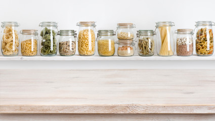 Wooden table on defocused background of groceries in glass jars