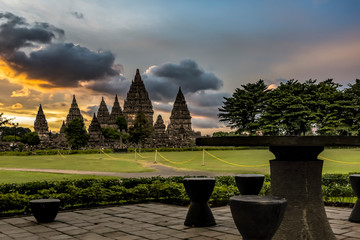 Prambanan temple view with green grass field foreground and cloudy sunrise; background