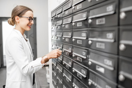Happy business woman opening mailbox in the walkhall of the modern residential building