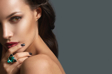 Gorgeous sexy Brunette Woman with evening Makeup wearing stylish green ring. Beautiful Professional Make-up. Red Lips, perfect eyebrows, face contouring. Grey background, copy space