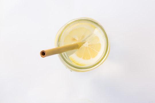 Lemon water and bamboo drinking straw.