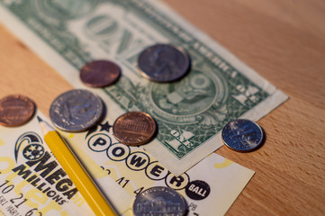 Close up photo of american lottery tickets with dollar bill, coins and pencil