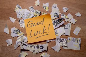 Closeup photo of motivation sticker note on teared up lottery tickets of Power Ball and Mega Millions