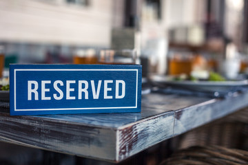 A wooden blue and white rectangular plate with the inscription Reserved stands on the corner of a gray aged vintage table. Concept of lunch in a restaurant, holiday, banquet