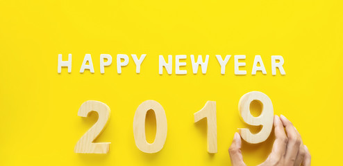 Symbol Celebration for 2019 year, wooden text Happy new Year 2019 on bright yellow paper background .Holiday Concept