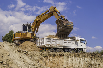 Excavator loads dump truck soil on the construction site