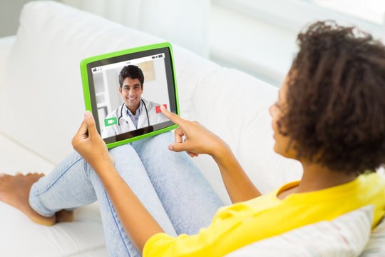medicine, technology and healthcare concept - african american young woman or patient having video chat with doctor on tablet pc computer at home