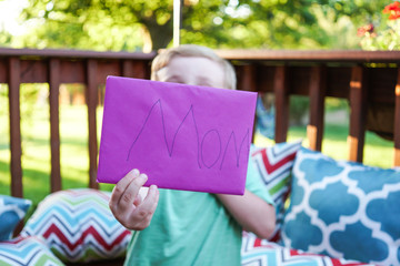 Child handing a Mother's Day card to his mom