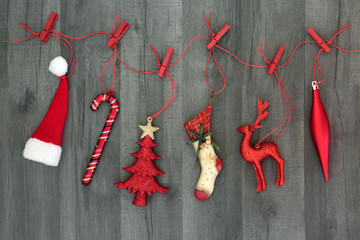 Christmas decorations and symbols of the festive season hanging on a red string line with pegs on rustic wood background. Christmas card for the festive season.